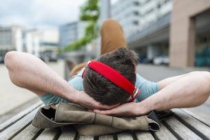 Relaxed young man lying on bench listening to musicの写真素材 [FYI04337173]