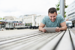 Smiling young man outdoors lying on bench using digital tablの写真素材 [FYI04337174]
