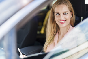 Portrait of smiling young businesswoman sitting in a carの写真素材 [FYI04337180]