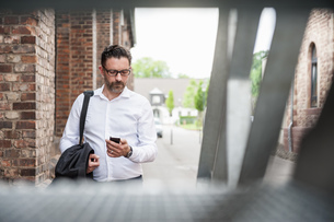 Businessman looking at cell phoneの写真素材 [FYI04337199]