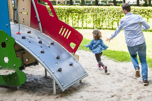 Father running with daughter on playgroundの写真素材 [FYI04337209]