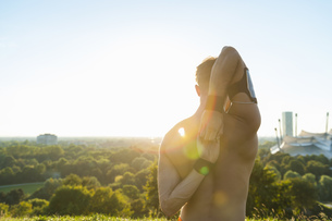 Barechested athlete stretching at sunsetの写真素材 [FYI04337217]