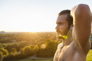 Barechested athlete with earbuds at sunsetの写真素材 [FYI04337219]