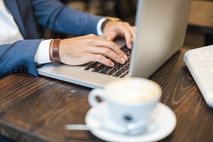 Close-up of businessman with coffee using laptop in a cafeの写真素材 [FYI04337228]