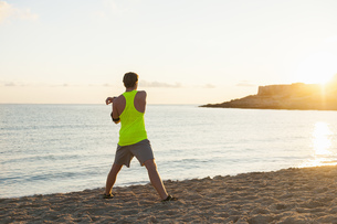Spain, Mallorca, Jogger at the beach in the morning, stretchの写真素材 [FYI04337230]