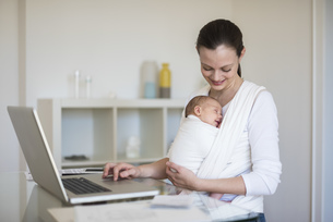 Mother with baby girl in sling working from homeの写真素材 [FYI04337231]