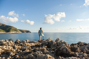 Spain, Mallorca, Jogger standing on rocky coastの写真素材 [FYI04337232]