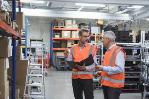 Two colleagues in factory hall wearing safety vests holdingの写真素材 [FYI04337247]