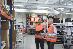 Two colleagues in factory hall wearing safety vests holdingの写真素材 [FYI04337248]