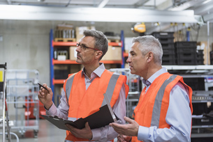 Two colleagues in factory hall wearing safety vests holdingの写真素材 [FYI04337249]