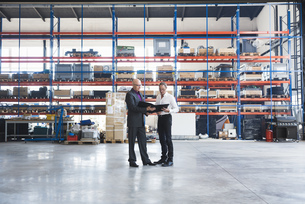 Two businessmen with clipboard on factory shop floorの写真素材 [FYI04337256]