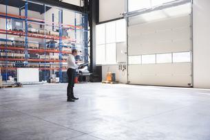 Man with documents on factory shop floorの写真素材 [FYI04337258]