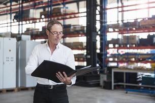 Man with documents on factory shop floorの写真素材 [FYI04337259]