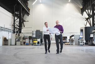 Two businessmen with plan walking in factory shop floorの写真素材 [FYI04337267]