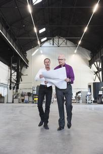 Two businessmen with plan walking in factory shop floorの写真素材 [FYI04337268]