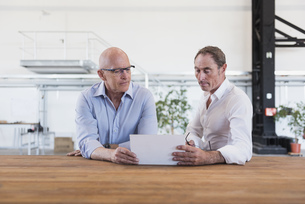 Two men sharing tablet in factoryの写真素材 [FYI04337275]