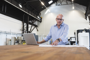 Man with laptop looking at plan on table in factoryの写真素材 [FYI04337279]