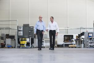 Two businessmen walking and talking in factory shop floorの写真素材 [FYI04337282]