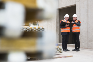 Two men wearing safety vests talking on construction siteの写真素材 [FYI04337287]