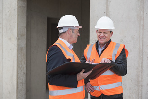Two men wearing safety vests talking on construction siteの写真素材 [FYI04337289]