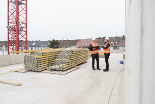 Two men wearing safety vests talking on construction siteの写真素材 [FYI04337290]