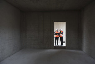 Two men wearing safety vests talking in building under constの写真素材 [FYI04337291]