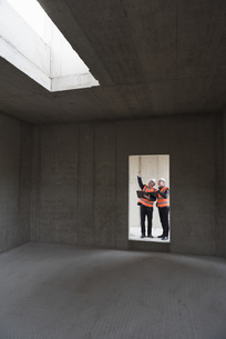 Two men wearing safety vests talking in building under constの写真素材 [FYI04337294]
