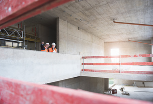 Two men wearing safety vests talking in building under constの写真素材 [FYI04337309]
