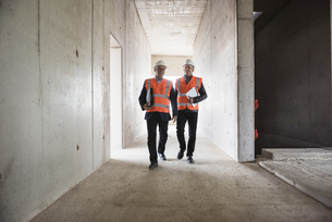 Two men wearing safety walking in building under constructioの写真素材 [FYI04337310]