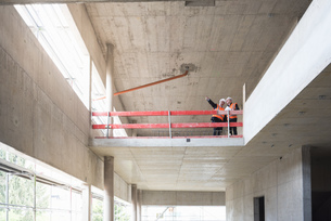 Two men wearing safety vests talking in building under constの写真素材 [FYI04337326]