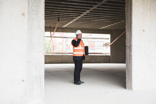Man on the phone wearing safety vest in building under constの写真素材 [FYI04337334]