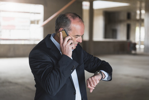 Businessman on cell phone in building under construction cheの写真素材 [FYI04337336]