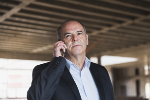 Businessman on cell phone in building under constructionの写真素材 [FYI04337338]