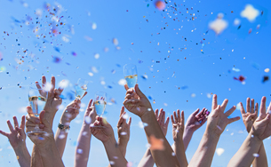 People exulting, Arms raised with champagne glasses, confettの写真素材 [FYI04337357]