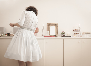 Young woman at the buffet on a retro style tea partyの写真素材 [FYI04337399]