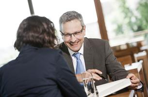 Businessman and businesswoman talking in restaurantの写真素材 [FYI04337409]