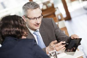 Businessman and businesswoman talking in restaurantの写真素材 [FYI04337412]