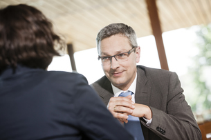 Businessman and businesswoman talking in restaurantの写真素材 [FYI04337413]