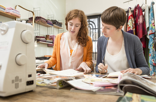 Two female fashion designers at her work deskの写真素材 [FYI04337423]