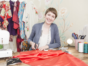 Portrait of smiling female fashion designer at her deskの写真素材 [FYI04337428]