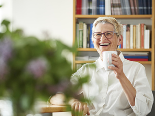 Portrait of laughing senior woman with cup of coffee at homeの写真素材 [FYI04337459]