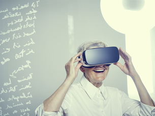Senior woman wearing Virtual Reality Glassesの写真素材 [FYI04337462]