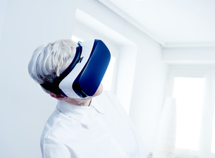 Senior woman wearing Virtual Reality Glassesの写真素材 [FYI04337464]