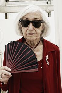 Germany, Bavaria, Munich, Senior woman with folding fan, porの写真素材 [FYI04337471]