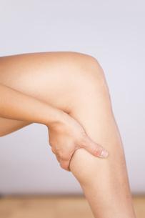 Germany, Freiburg, Mid adult woman massaging her knee, closeの写真素材 [FYI04337478]