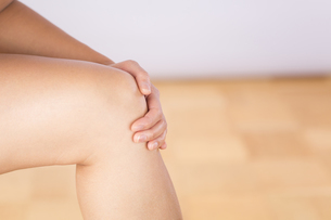 Germany, Freiburg, Mid adult woman holding her knee, close uの写真素材 [FYI04337480]