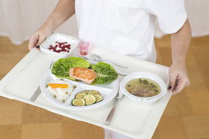 Germany, Young woman holding patient tray with main meal, clの写真素材 [FYI04337483]