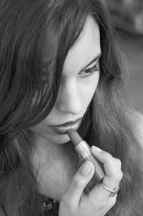 Young woman applying lipstickの写真素材 [FYI04337485]
