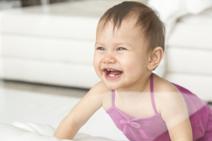 Laughing baby girl crowling on the floorの写真素材 [FYI04337522]