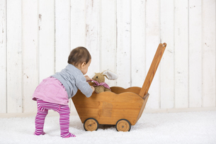 Little girl playing with soft toy in doll cartの写真素材 [FYI04337523]